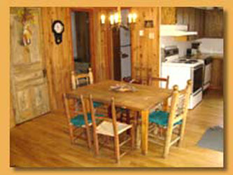 Mont-Tremblant Wood Cottage for rent dining room with stone fireplace